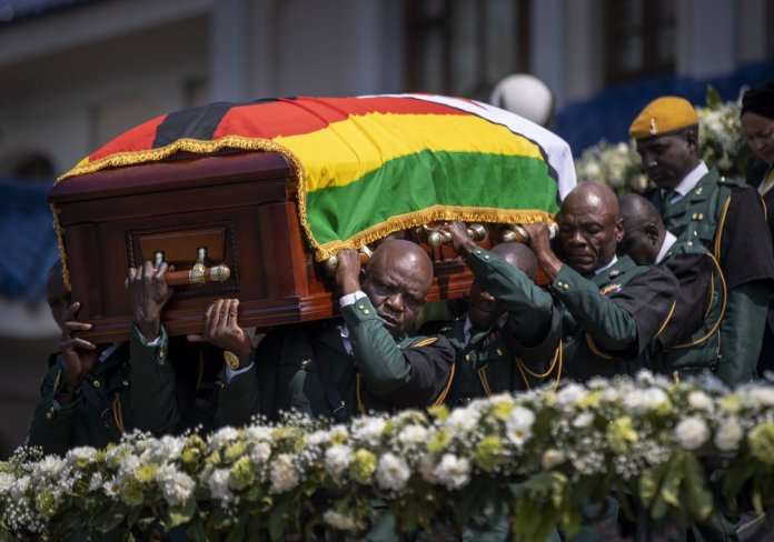 The casket of former president Robert Mugabe is carried by the presidential guard to an air force helicopter for transport to a stadium where it will lie in state, at his official residence in the capital Harare, Zimbabwe Friday, Sept. 13, 2019. The ongoing uncertainty of the burial of Mugabe, who died last week in Singapore at the age of 95, has eclipsed the elaborate plans for Zimbabweans to pay their respects to the former guerrilla leader at several historic sites. (AP Photo/Ben Curtis)