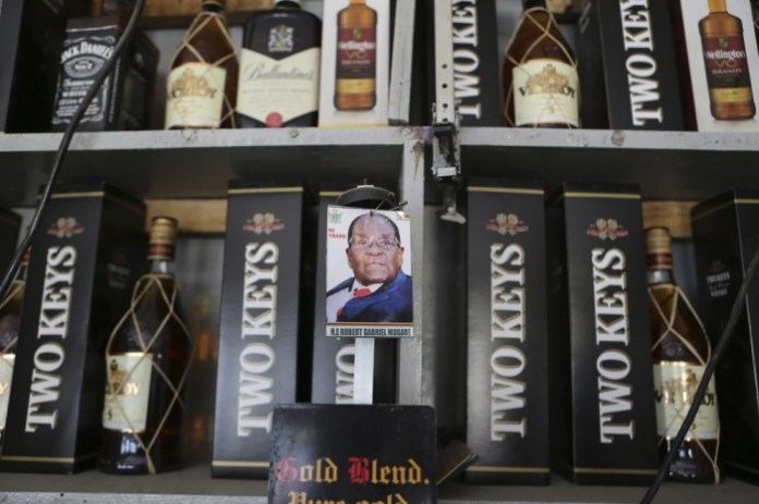A portrait of former Zimbabwean President Robert Mugabe is seen a bar in Zvimba about 100 kilometres north west of the capital Harare, Friday, Sept, 27, 2019. Zimbabwe's former president Robert Mugabe is expected to be buried on Saturday, a family spokesperson said Friday, after three weeks of drama over the former strongman's final resting place.(AP Photo/Tsvangirayi Mukwazhi)