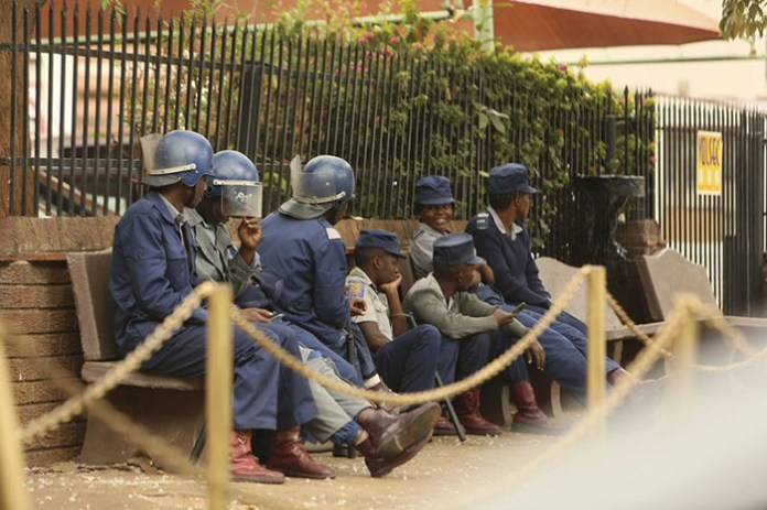 "Zimbabwe riot police sit outside the hospital in Harare, Wednesday Sept. 25, 2019, where the head of the Zimbabwe Hospital Doctors Association Dr. Peter Magombeyi is currently receiving medical care. Magombeyi who is desperate to leave the country for medical treatment after his recent abduction has been blocked after police approached the High Court asserting he is ""unfit to travel"". (AP Photo/Tsvangirayi Mukwazhi)"