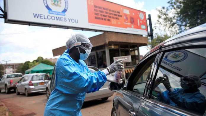 A health worker screens and sanitises visitors to prevent the spread of coronavirus disease (COVID-19) outside a hospital in Harare, Zimbabwe March 26, 2020. (Credit: Philimon Bulawayo/Reuters)