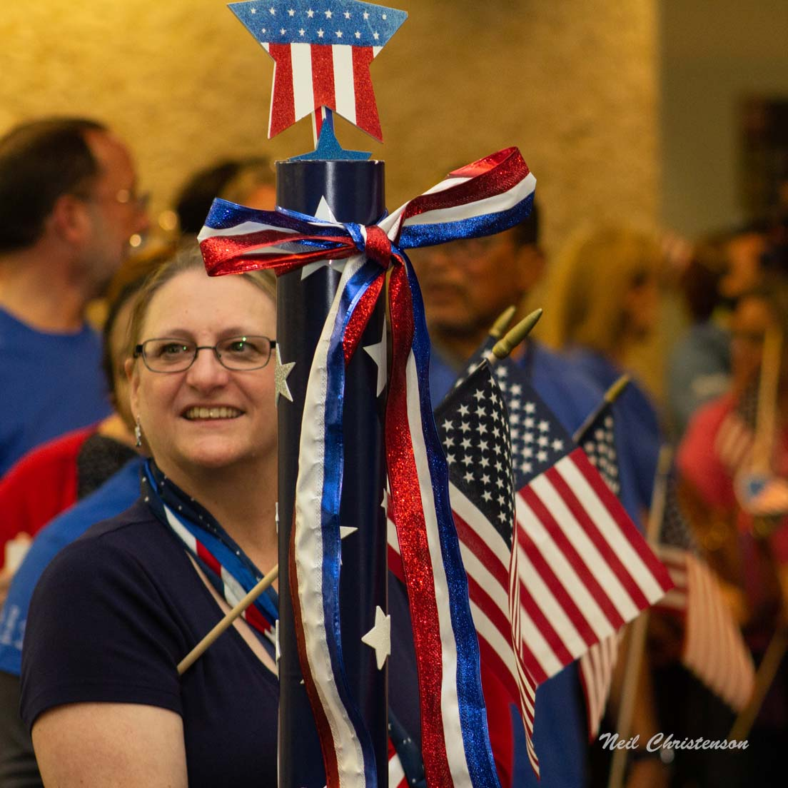 A woman standing by a patriotically-decorated stanton with a crowd behind her.