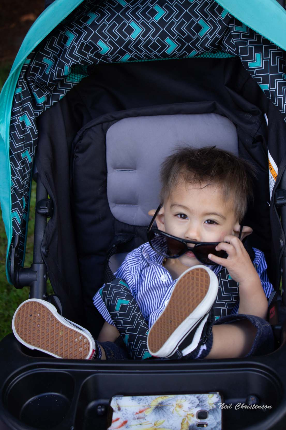 A toddler pulling down his sunglasses while sitting in a stroller.