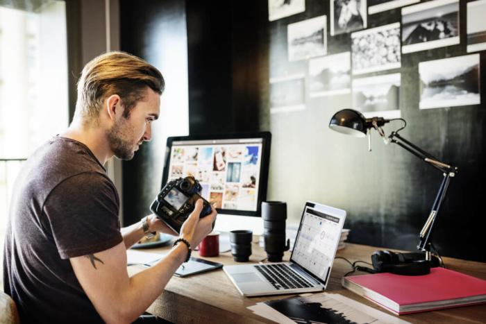 fotógrafo em frente ao laptop vendendo imagens dinheiro - fot C3 B3grafo em frente ao laptop vendendo imagens 700x467 - Como Ganhar Dinheiro na Internet: As 55 Melhores Maneiras (2021)