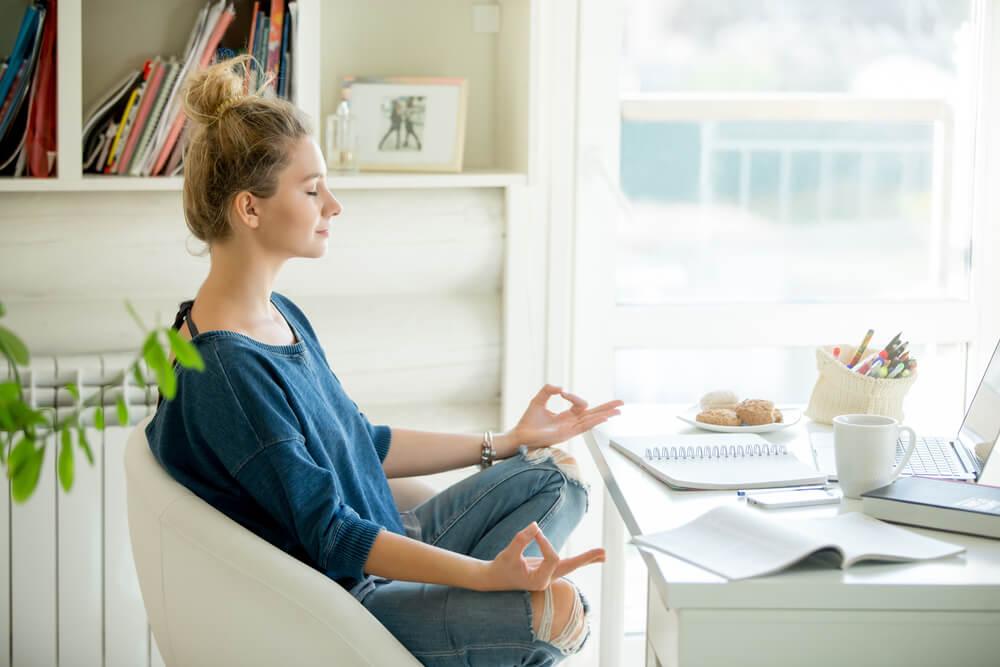 moça meditando em home office