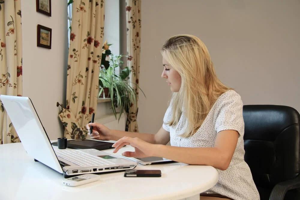 moça trabalhando ao notebook em mesa durante o dia
