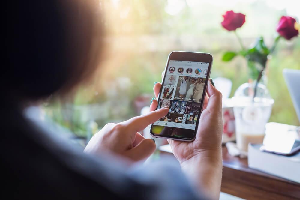 mulher vendo instagram stories instagram - word image 49 - Instagram Stories: O Que É, Como Funciona e Dicas Práticas