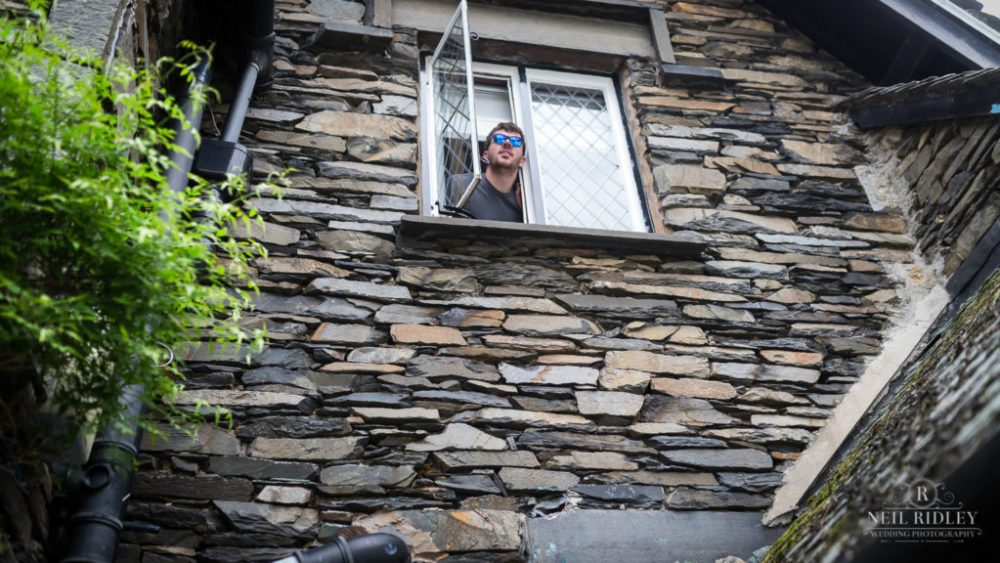 Groom sticks head through window during Groom Prep at Broadoaks Country Hotel Lake District