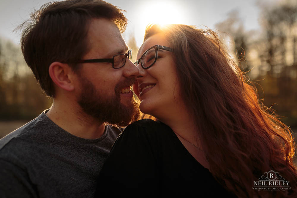 Lancashire Pre Wedding Shoot at Scorton Lake, a young couple face to face backlit by the sun