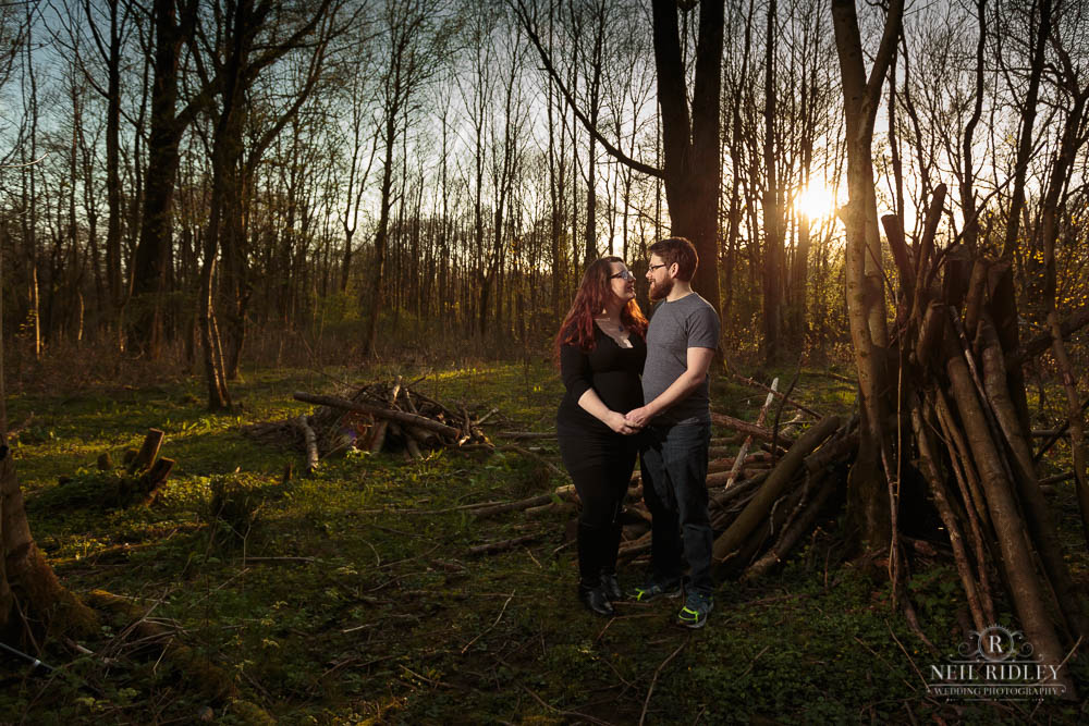 Lancashire Pre Wedding Shoot at Scorton Lake, a young couple hold hands in a wooded clearing