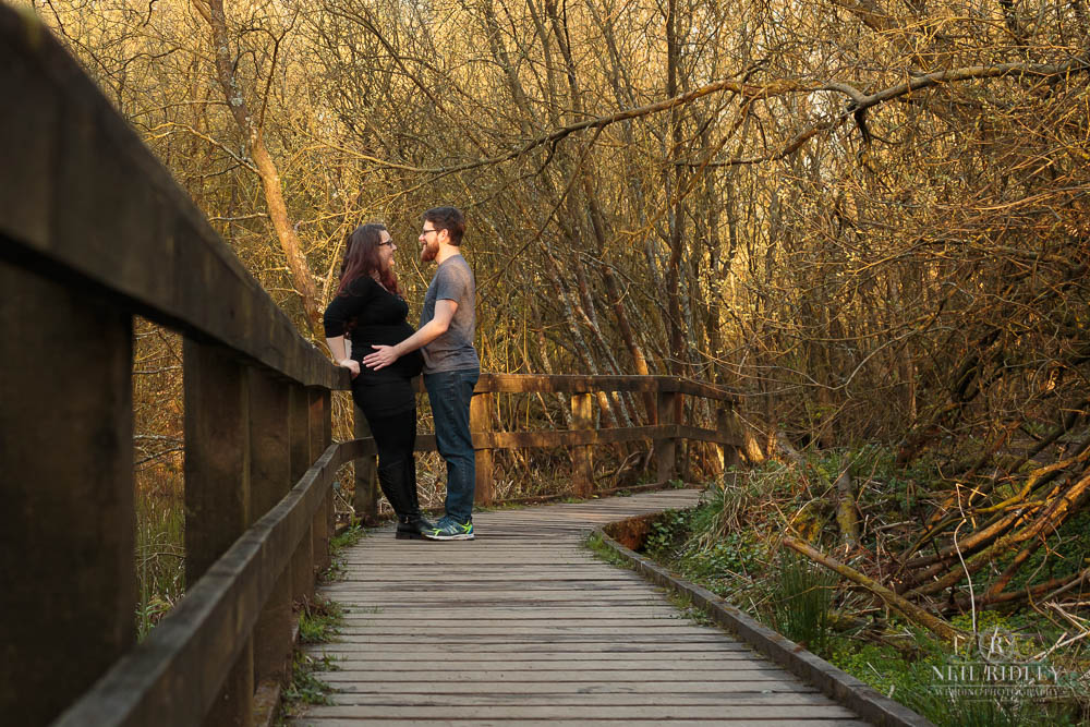Lancashire Pre Wedding Shoot at Scorton Lake, a young couple embrace on a raised wooden walkway