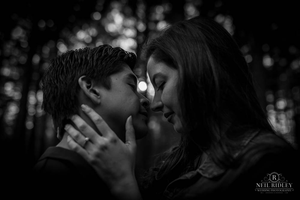Black and white image of young couple face to face in a forest