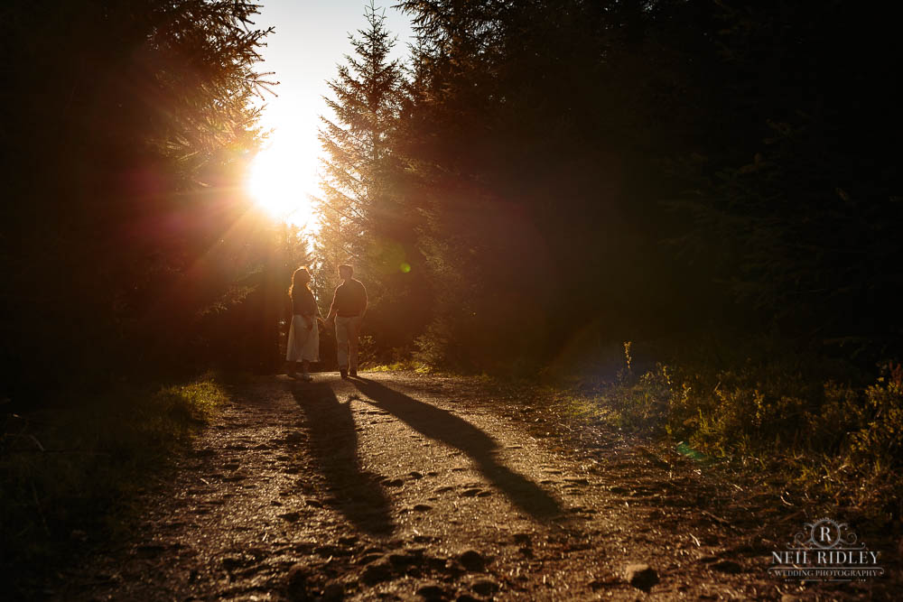 Young couple walking on sunlit trail through a forest
