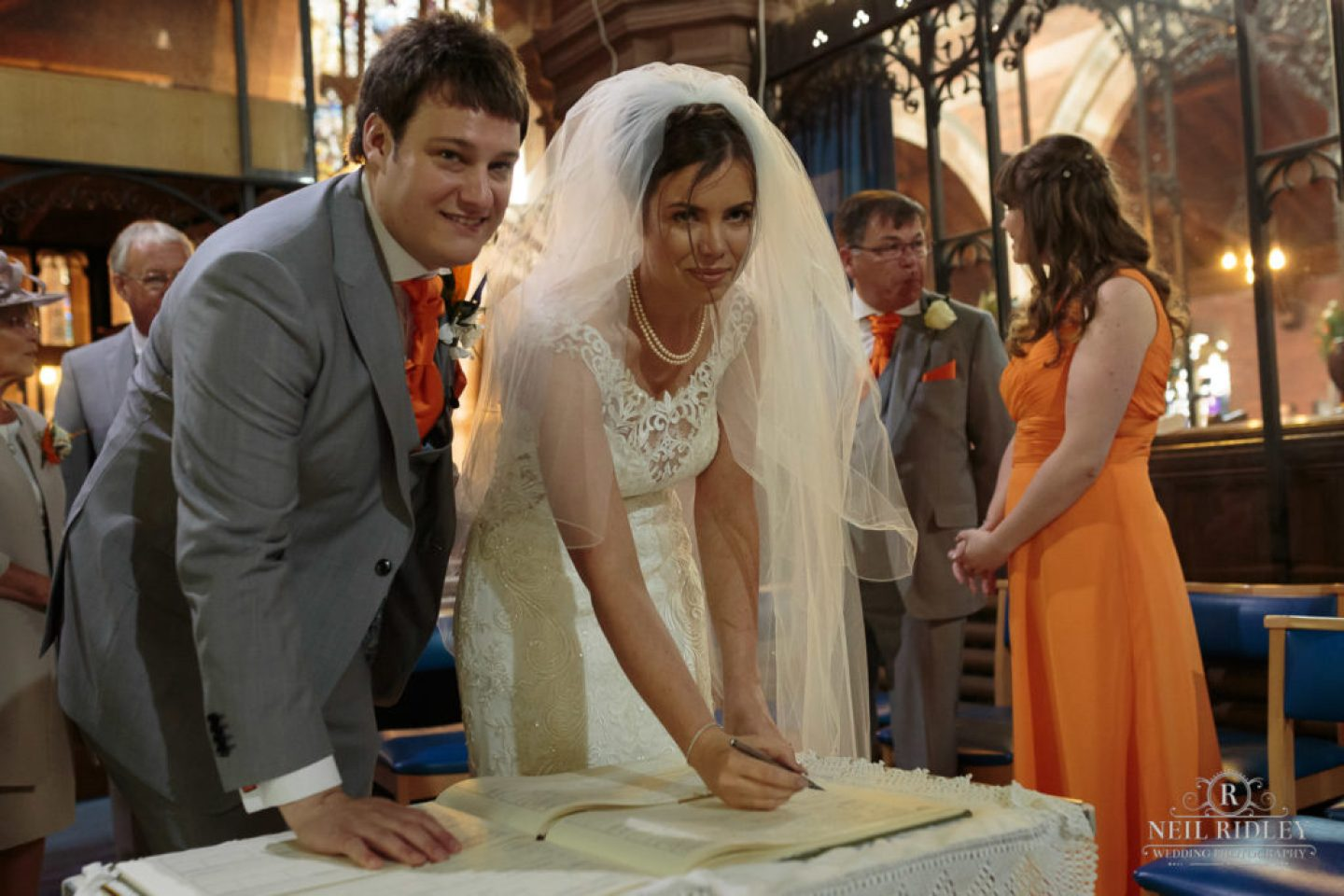 Bride and Groom sign the registrar in church at St Thomas Church in St Annes-on-Sea