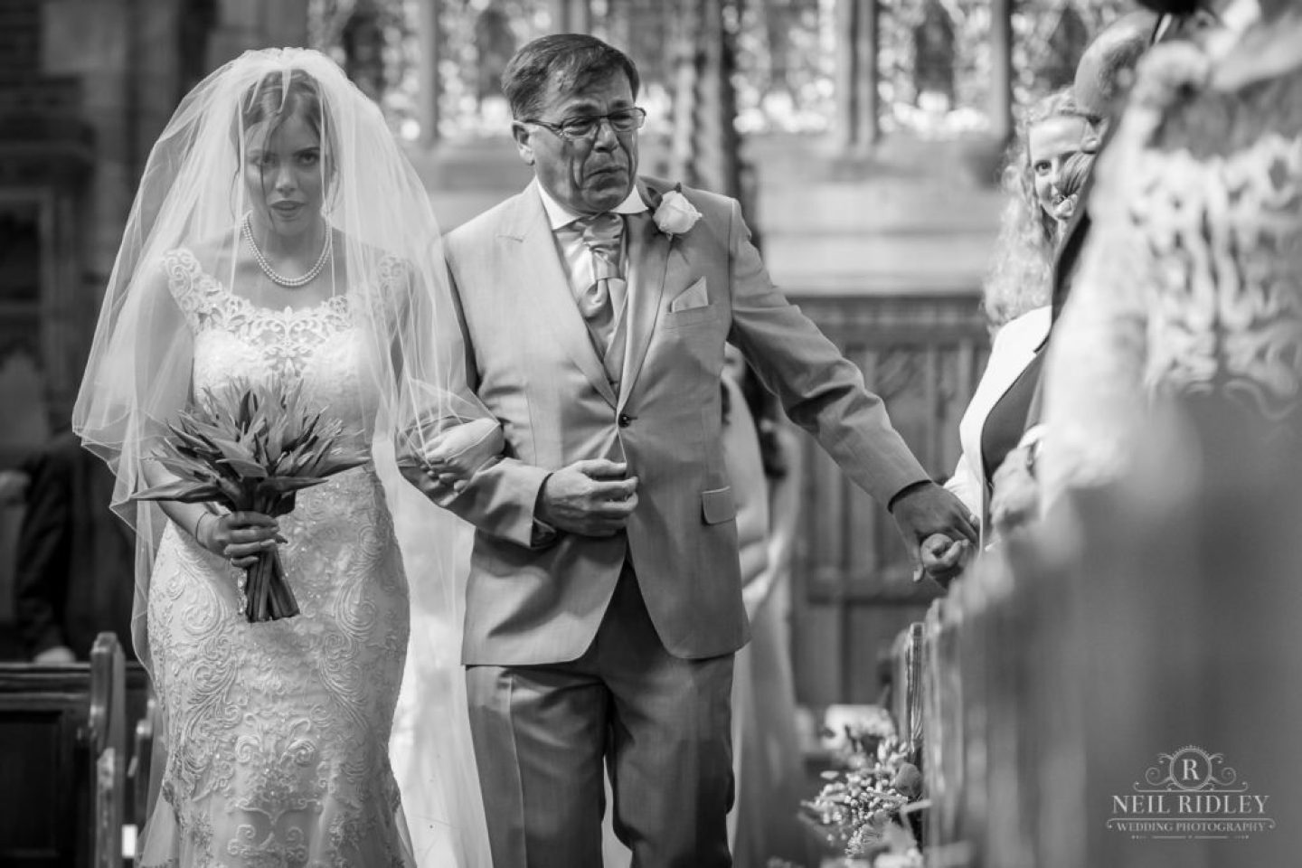 Black and white image of Bride and her Father walking down the aisle in church, with father crying at St Thomas Church in St Annes-on-Sea