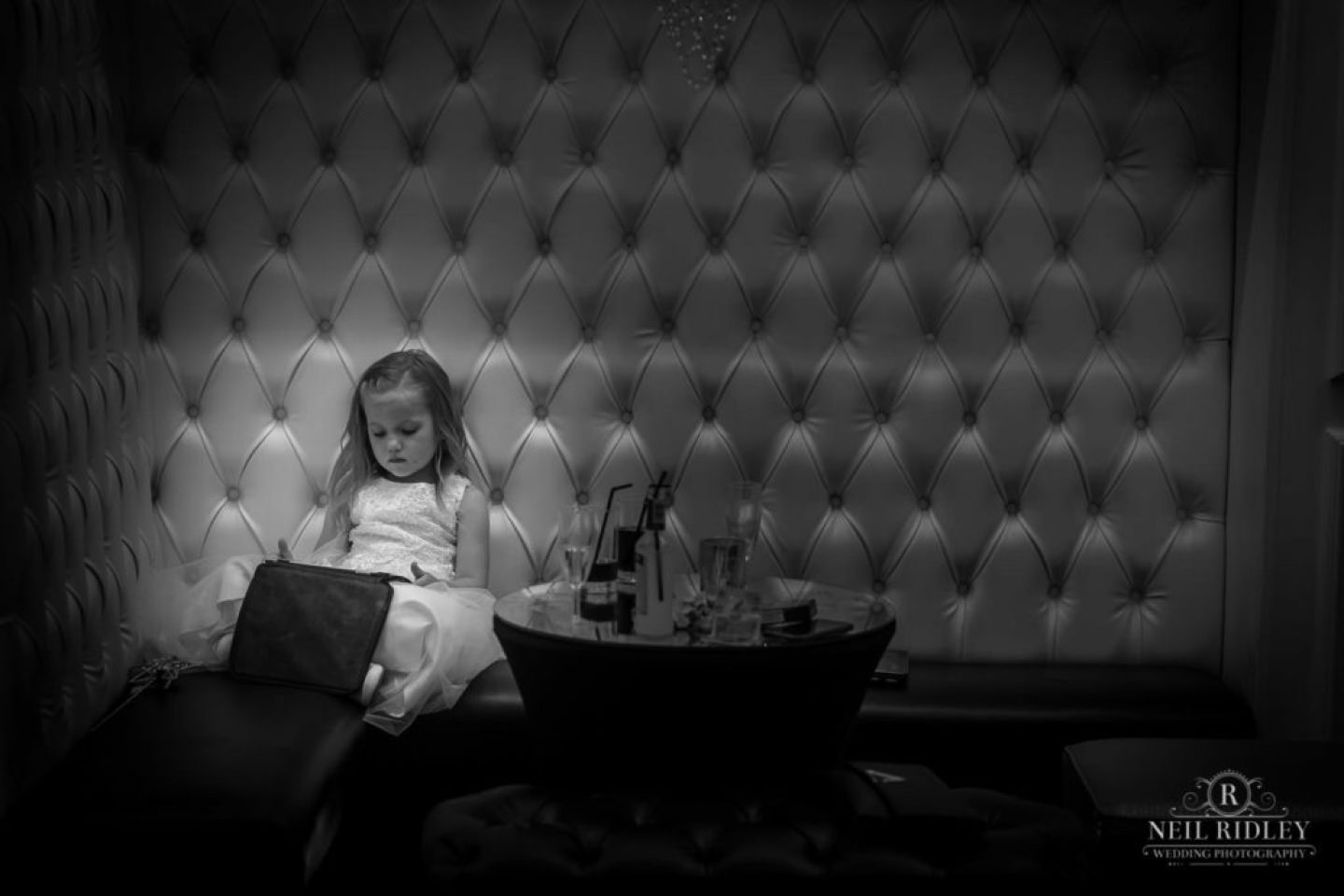 Black and white image of young girl sat in a booth at The Park House Hotel, Blackpool
