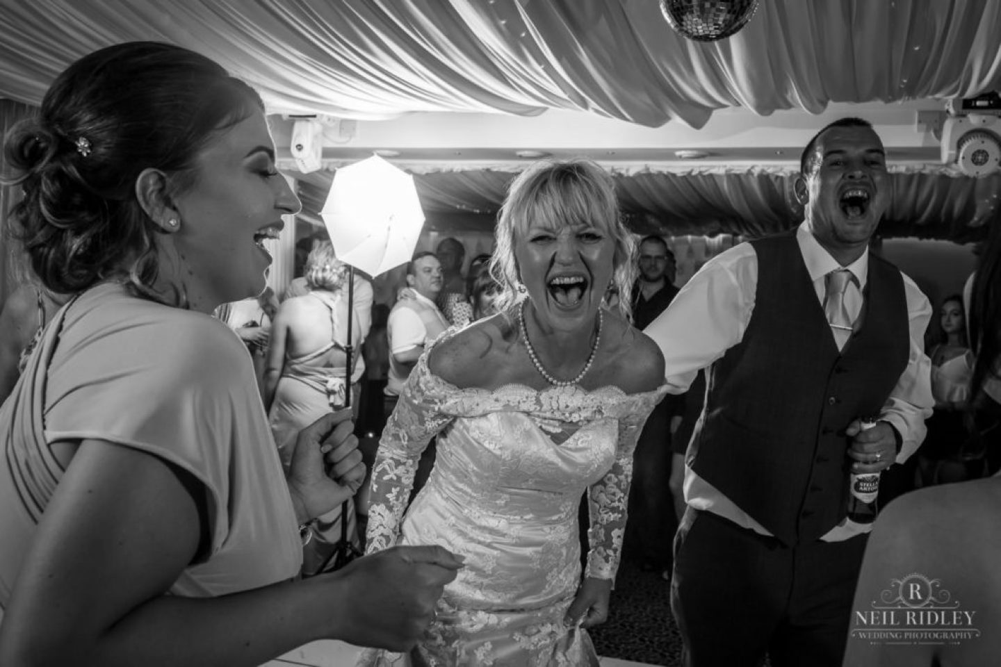 Black and white image of bride and groom laughing looking at the camera at The Park House Hotel, Blackpool