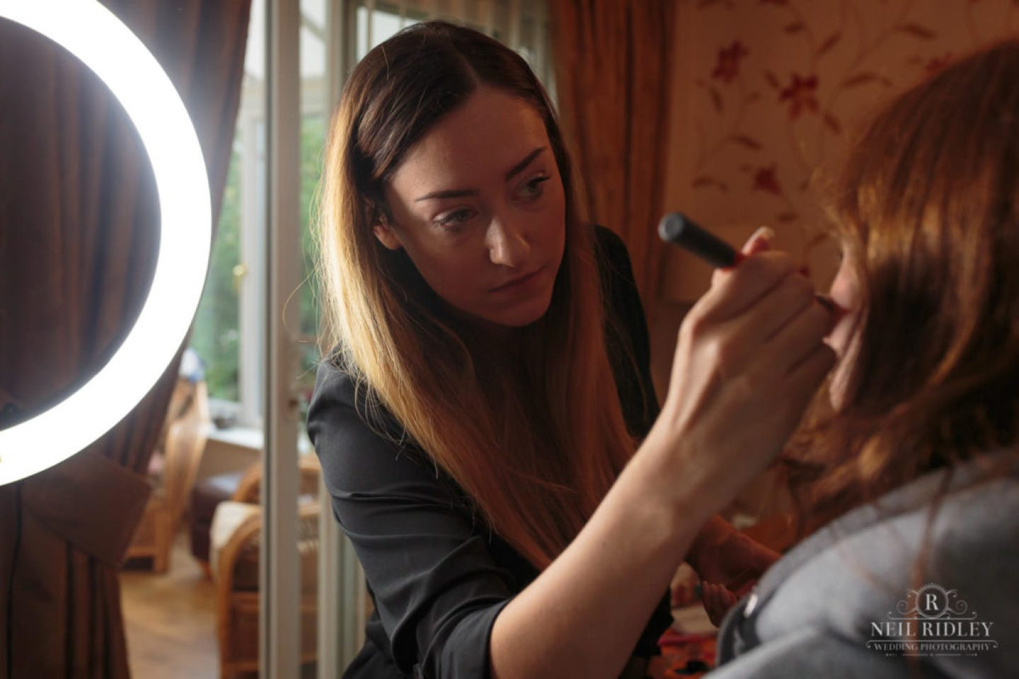 Make up artist applying makeup with a brush during Bridal Prep
