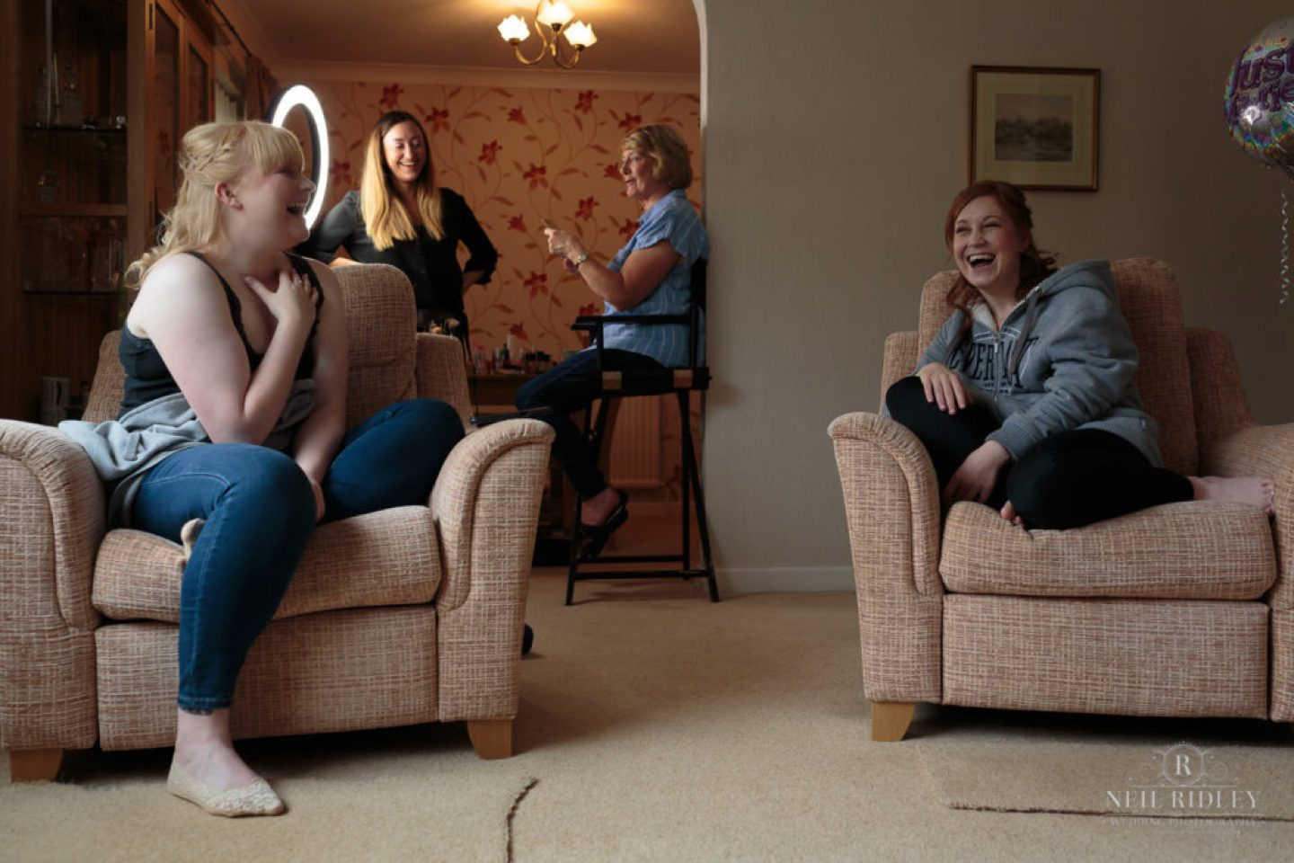 Bridal prep with bride and bridesmaids sat in living room laughing
