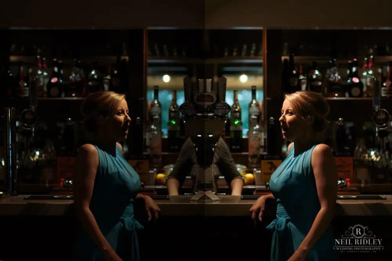 Bridesmaid reflected in mirror at The Mill at Conder Green