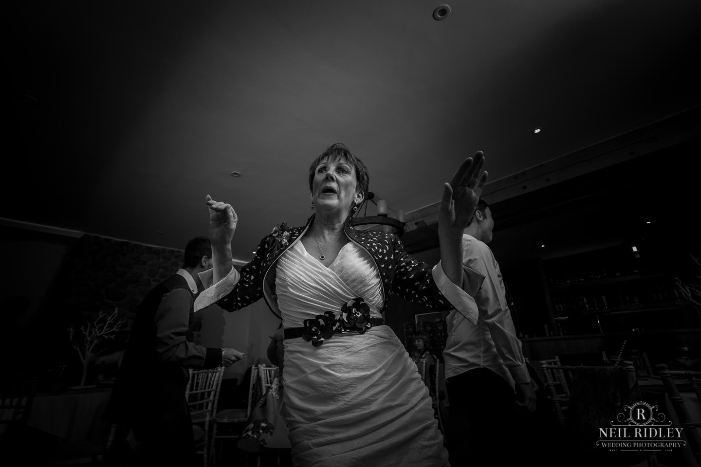 Black and white image of the mother of the Bride dancing on the dancefloor at The Mill at Conder Green