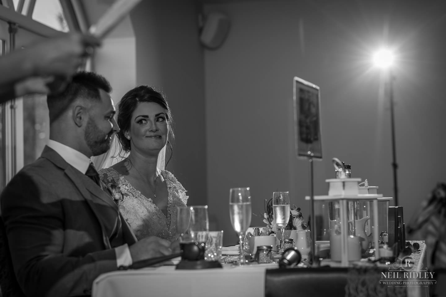 Black and white image of bride and groom sat at the top table at The Mill at Conder Green