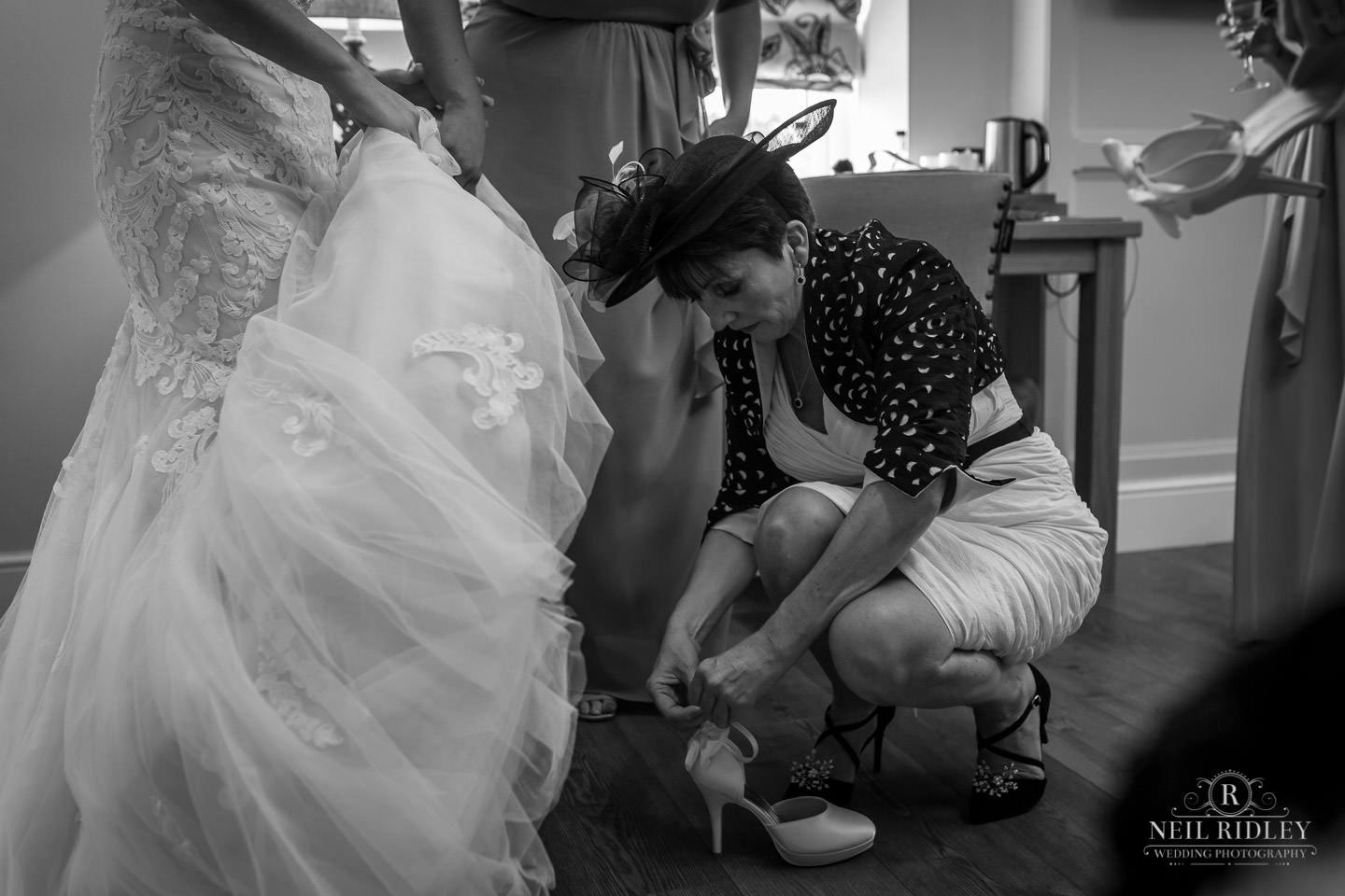 Mother of the bride fastens Brides shoe during Bridal Prep at The Mill at Conder Green