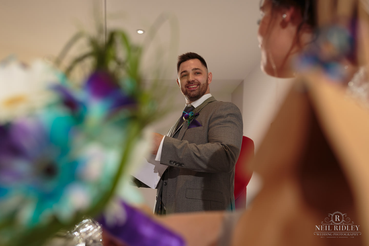 Groom looks at his bride whilst delivering his sppech at The Mill at Conder Green