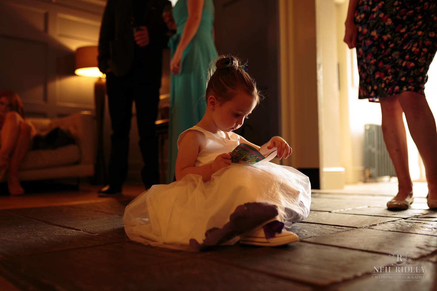 Young bridesmaid sits on the floor reading a book at The Mill at Conder Green