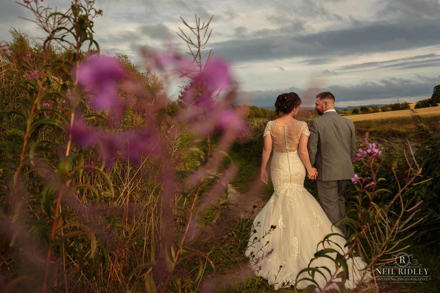 Bride and Groom walk along a country path at The Mill at Conder Green