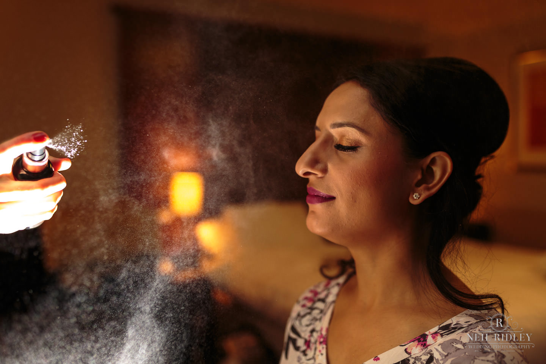 Merrydale Manor Wedding Photographer - Bride being sprayed with makeup fix