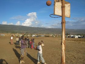 BAsketball being played on a dirt court in Africa
