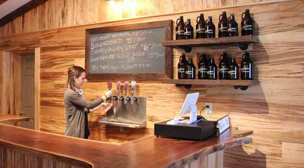 Tap Room interior. A long wooden bar, chalkboard, four taps, and young woman pouring a beer into a pint glass.