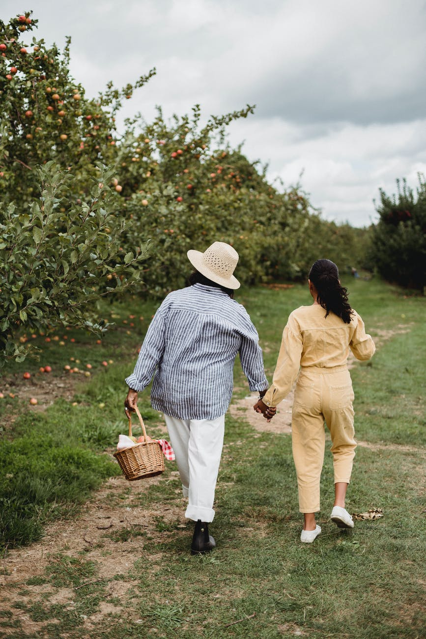 mother and daughter walking together near apple trees