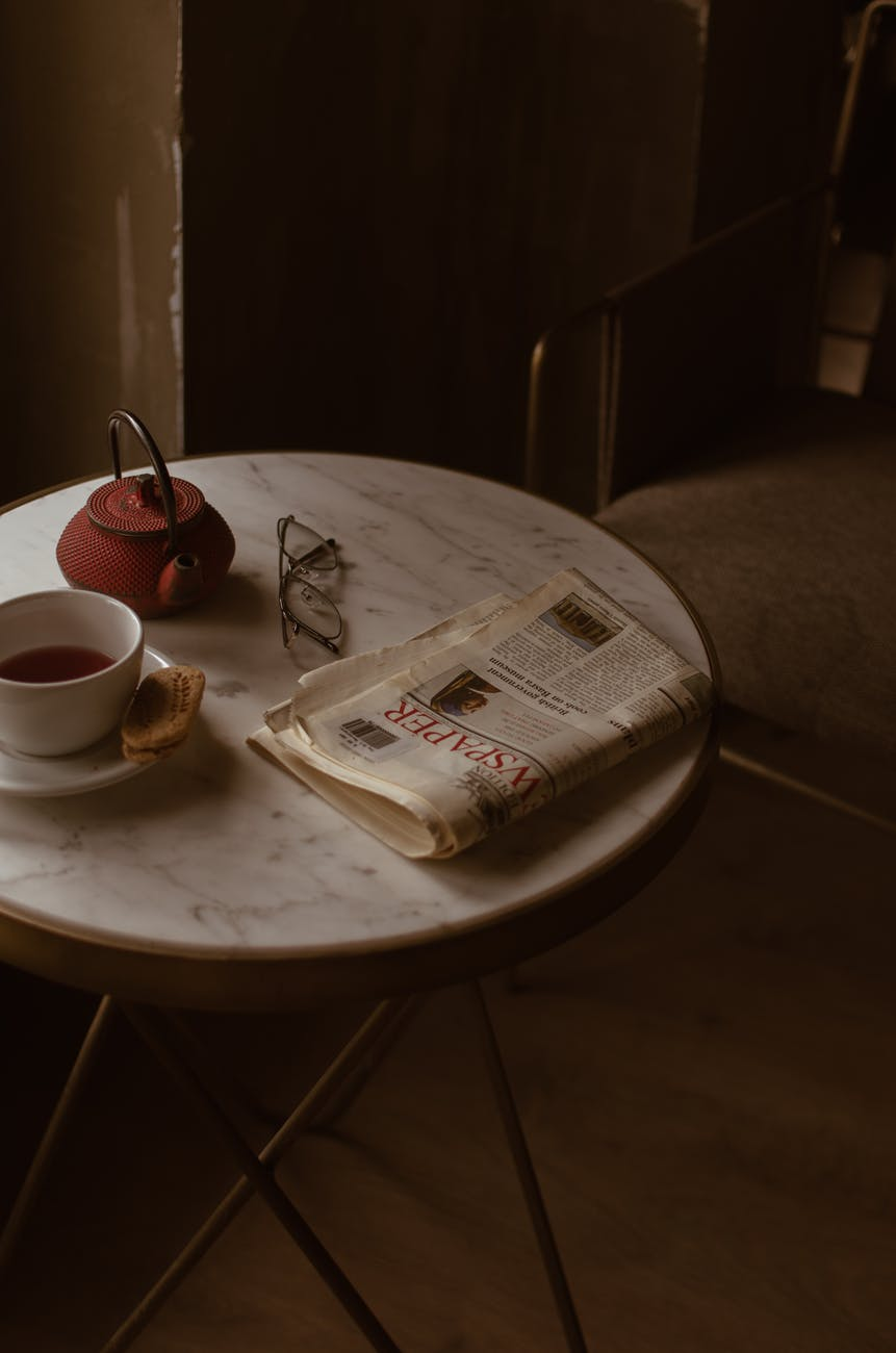 comfortable chair near round table with newspaper and tea set