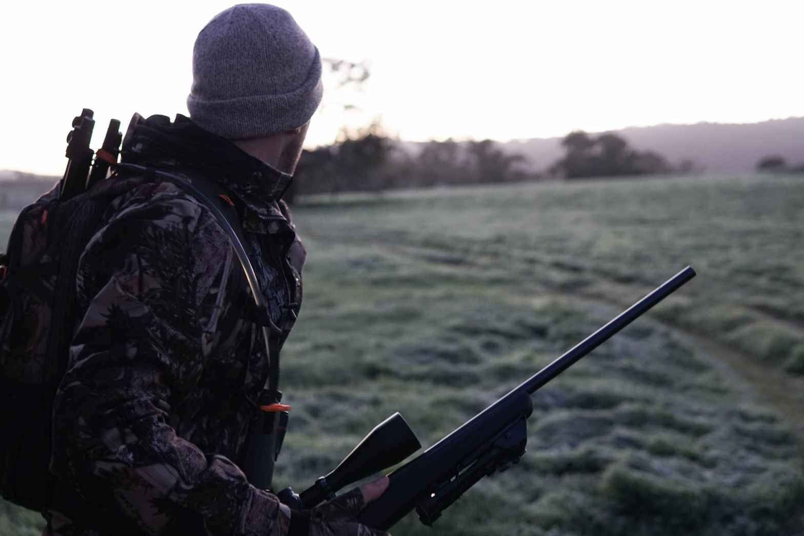 man wearing gray and black camouflage jacket holding rifle walking on grass field