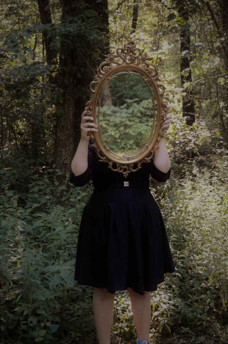 woman holding mirror against her head in the middle of forest