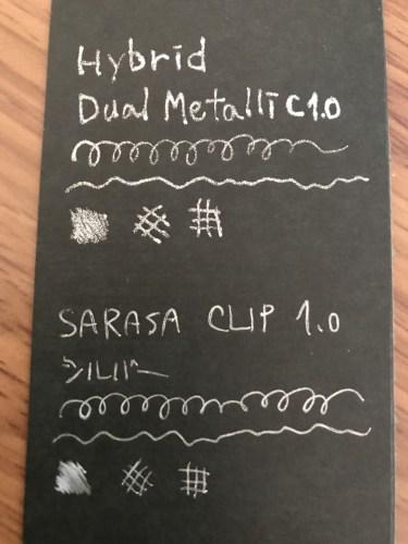 銀ペン黒の紙に描いた字