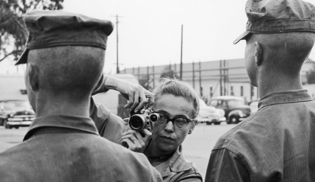Vakmerő nő a frontvonalban: fényképezőgép, bozótkalap és gyöngy fülbevaló