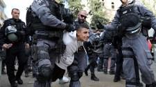 Izraeli rendőr egy békésen tüntető nő arcába vág