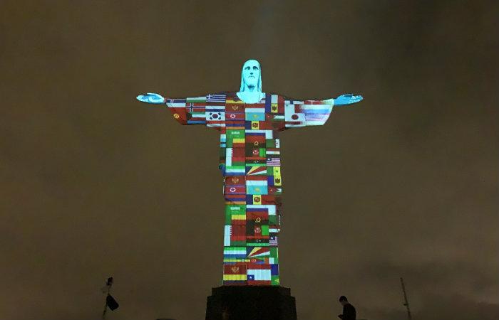 Cristo Redentor é iluminado com 150 bandeiras de países afetados por coronavírus