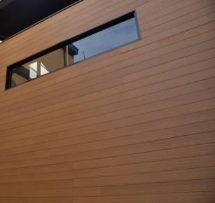 Fachada frontal edifico revestida con madera sintética