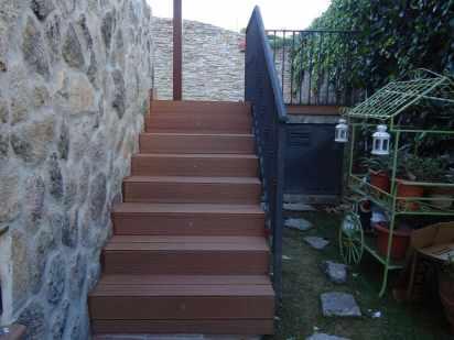 Escalera revestida con tarima sintética exterior Wood con focos de luz.