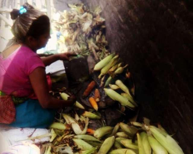 Street vendor preparing corn.