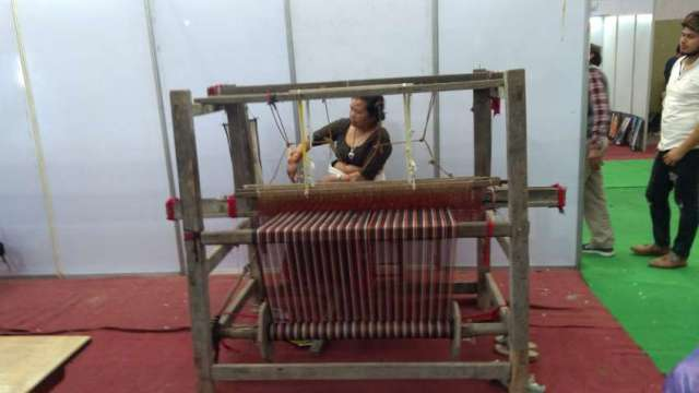Women weaves cloth at a handloom in Made in Nepal Product and Service Exhibition held at Bhrikutimandap, Kathmandu.