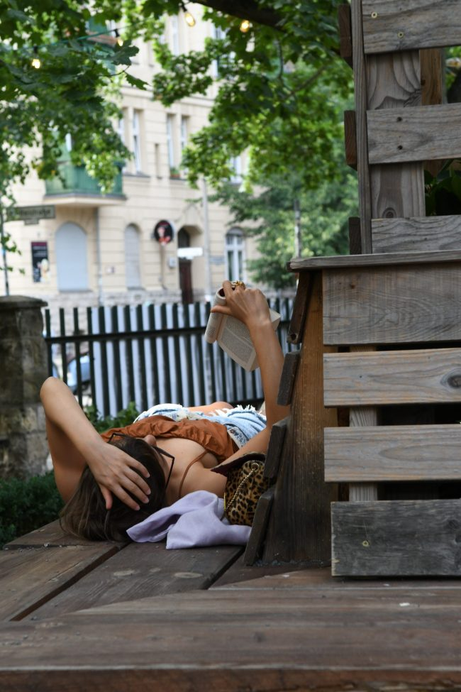 A woman wearing cut-off shorts and a brown tank top, lying on her back on wooden steps, holding a paperback above her face to read. A wood-toned picket fence lines the property, with a city street beyond.