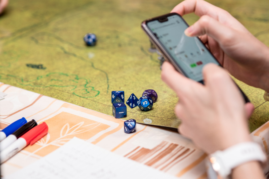 Girl Using The Smartphone During A Role Playing Game Of Dungeons And Dragons. Dices On The Green Battlefield