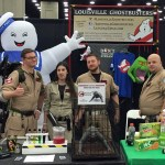 4 members of the Louisville Ghostbusters pose in jumpsuit costumes with props