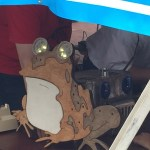 Wood cut depiction of cartoon character Hypno Toad with moving LED eyes.