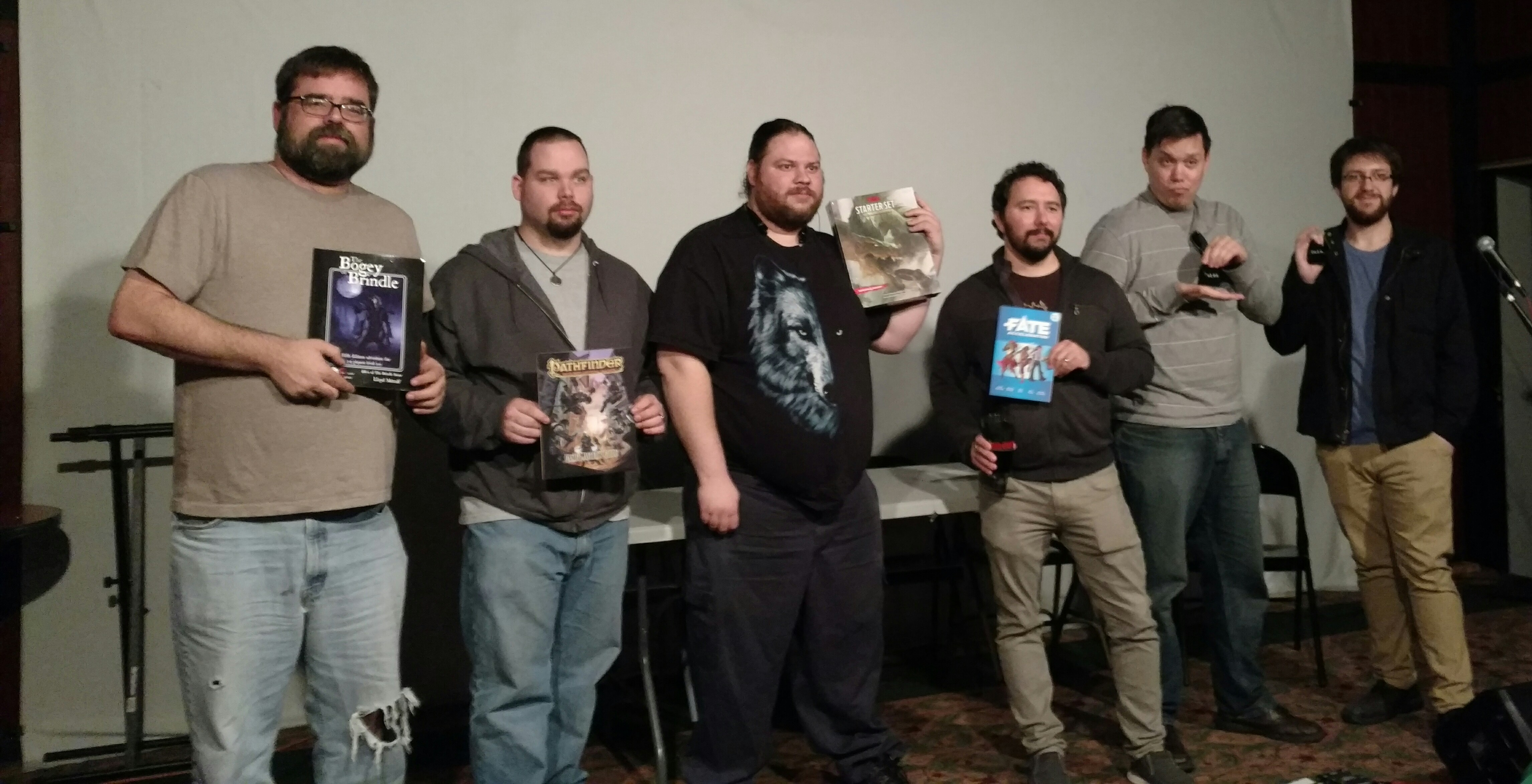 Audience winners from our GM Masterclass workshop event holding dice, game manuals and other giveaway prizes.