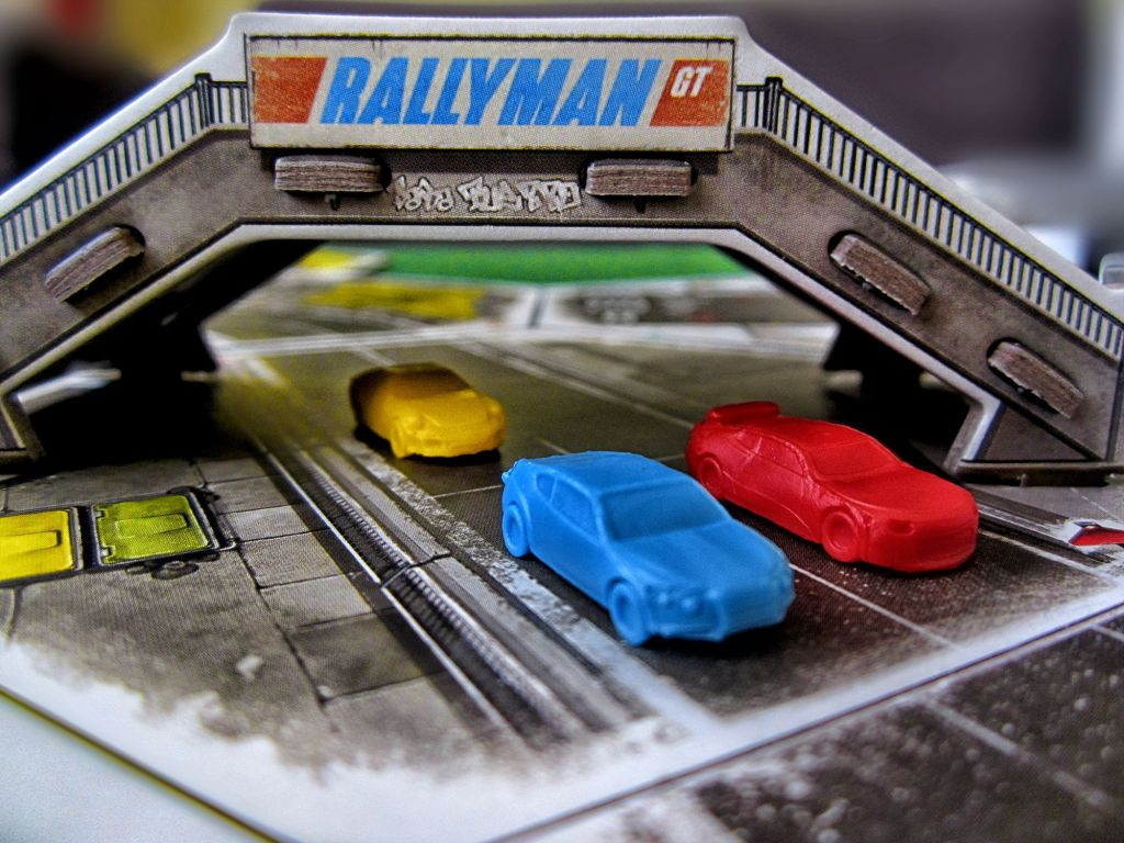 Rallyman: GT board game, featuring cars racing on a track as they pass under an overpass.